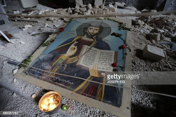 A picture taken on May 12 2014 shows a damaged painting of Jesus Christ on the ground of Syriac Orthodox Um alZinar church in the Christian Hamidiyeh...