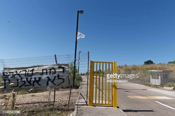 Picture taken on May 12, 2019 shows a sign put by residents of a new Israeli settlement in the occupied Golan Heights at the entrance gate to the...