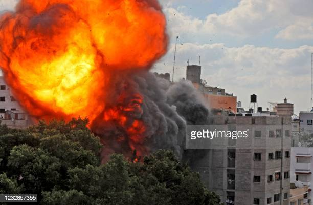Picture taken on May 13, 2021 shows a ball of fire engulfing the Al-Walid building which was destroyed in an Israeli airstrike on Gaza city early in...