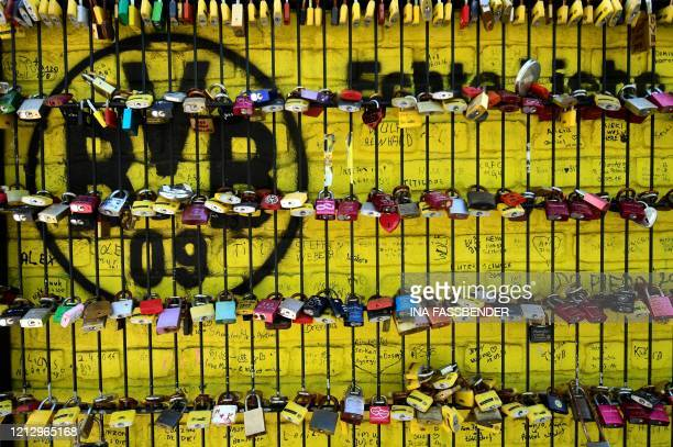 Picture taken on May 14, 2020 shows love locks on a fence in front of the Signal Iduna Park stadium of Bundesliga football club Borussia Dortmund in...