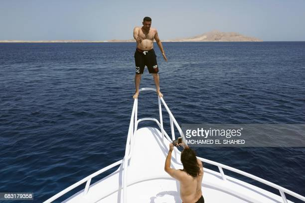 A picture taken on May 14 shows tourists taking a picture on a diving boat in the Egyptian Red Sea resort of Sharm elSheikh / AFP PHOTO / MOHAMED...