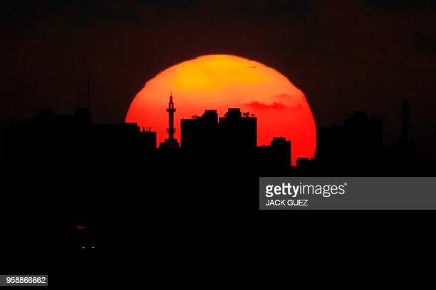 TOPSHOT A picture taken on May 15 from the southern Israeli kibbutz of Nahal Oz shows the sun setting over the skyline of Gaza City