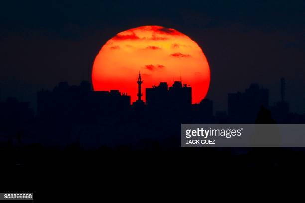 A picture taken on May 15 from the southern Israeli kibbutz of Nahal Oz shows the sun setting over the skyline of Gaza City
