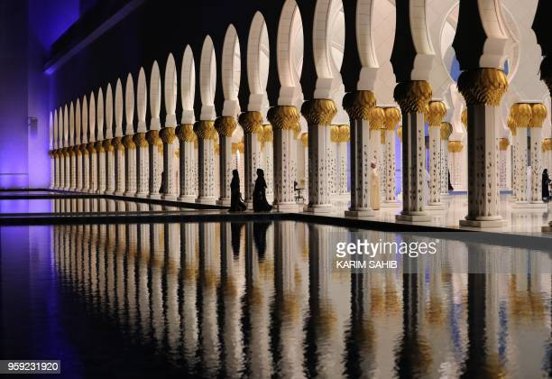 TOPSHOT A picture taken on May 16 2018 shows people walking at the Sheikh Zayed Grand Mosque in Abu Dhabi as Muslims start the holy fasting month of...