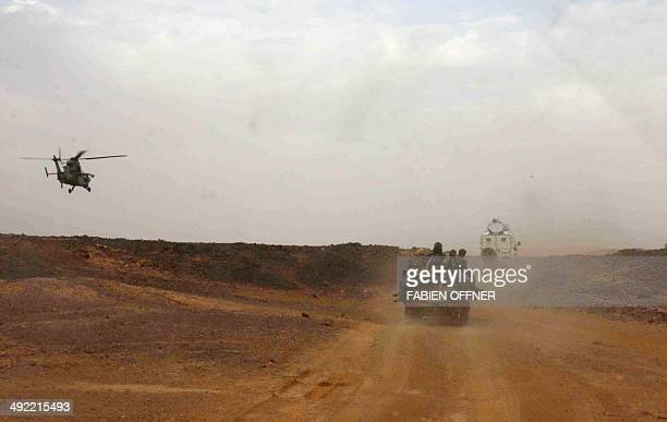 A picture taken on May 17 2014 shows an helicopter of the French army escorting a vehicule transporting Mali's Prime Minister Moussa Mara from Gao to...