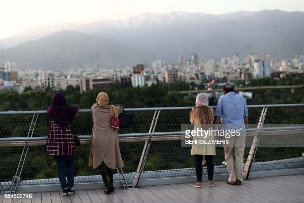 A picture taken on May 18 2017 shows Iranians looking at the skyline of northern Tehran from the Nature bridge in the capital Tehran on the eve of...