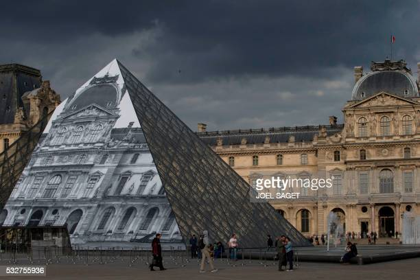 TOPSHOT A picture taken on May 19 2016 in Paris shows the Louvre Pyramid covered with a giant photograph of the museum by French artist and...