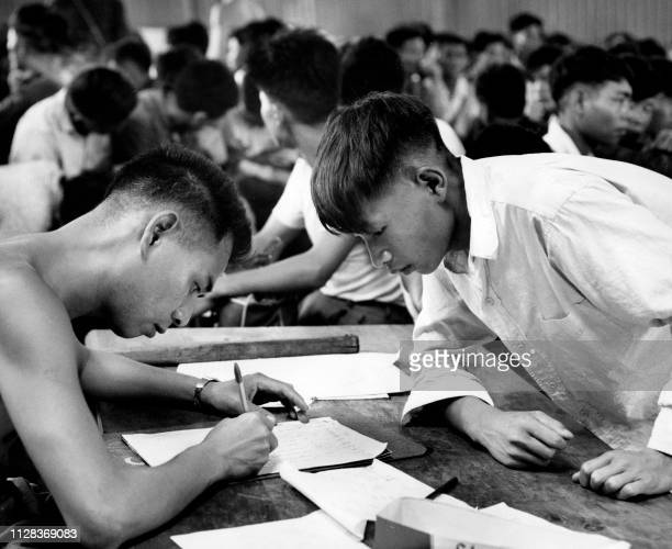 Picture taken on May 1962 showing Chinese refugees giving their identity to office employee in Hong Kong During the famine caused by The Great Leap...