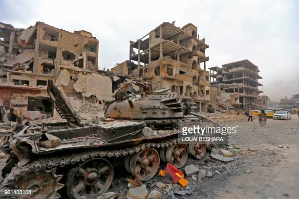 TOPSHOT A picture taken on May 22 2018 shows a destroyed tank in front of damaged buildings in the Hajar alAswad neighbourhood on the southern...