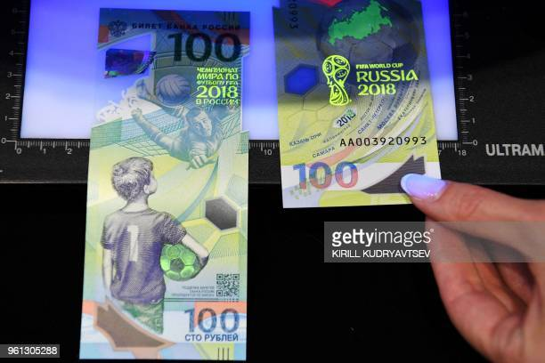 A picture taken on May 22 2018 shows the commemorative 100ruble banknote for the 2018 FIFA World Cup football tournament Some 20 million polymer...