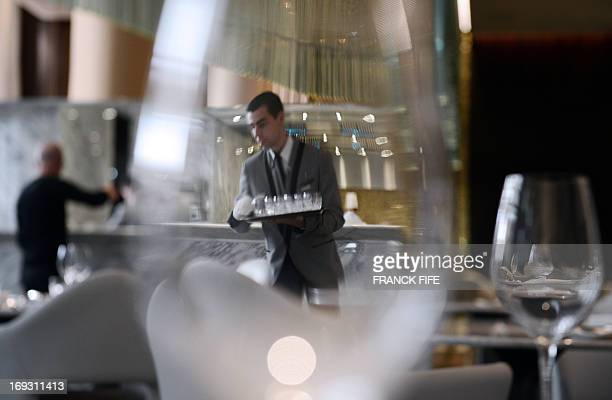 A picture taken on May 22 shows a server as seen through a wine glass at the restaurant 'La Scene' of the luxury hotel 'Prince de Galles' in Paris...