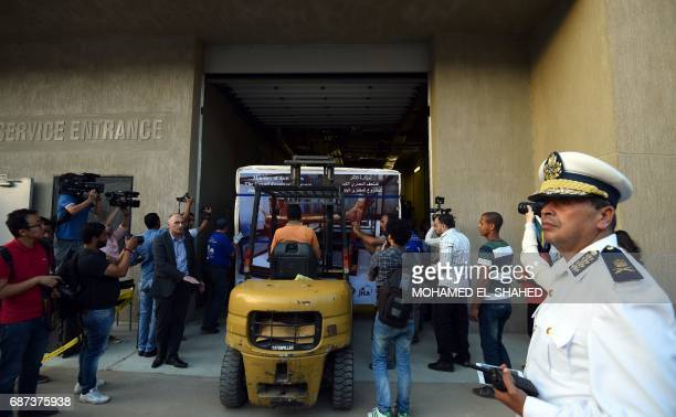 A picture taken on May 23 2017 shows the gilded bed of the ancient Egyptian boyking Tutankhamun arriving from the Egyptian Museum in the centre of...