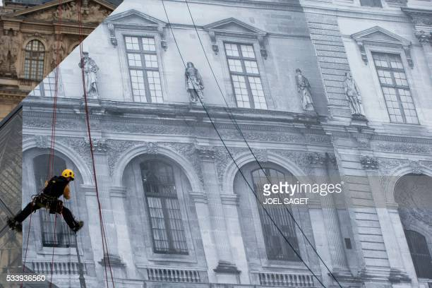 A picture taken on May 24 2016 in Paris shows an employee at work to cover the Louvre Pyramid with a giant photograph of the museum by French artist...