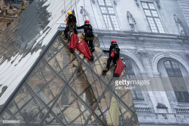 A picture taken on May 24 2016 in Paris shows employees at work to cover the Louvre Pyramid with a giant photograph of the museum by French artist...