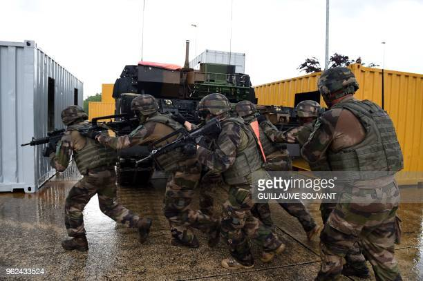 Picture taken on May 25, 2018 shows soldiers running by a Char Leclerc tank during a military exercise during a visit by French Defence Minister to...