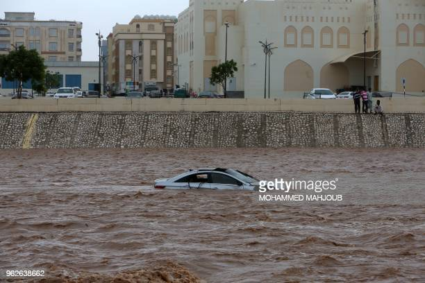 TOPSHOT A picture taken on May 26 shows a car stuck in a flooded street in the southern city of Salalah as the country prepares for landfall of...