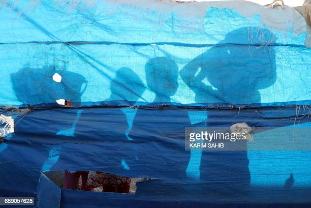 TOPSHOT A picture taken on May 27 2017 shows the silhouettes of displaced children queuing up for water rations on the first fasting day of the...