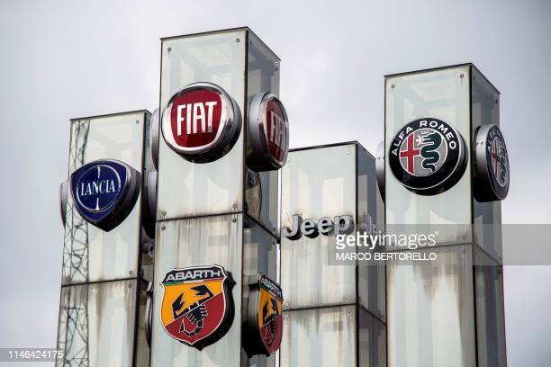 A picture taken on May 27 2019 at a car dealer in Turin shows the logos of Lancia Fiat Abarth Jeep and Alfa Romeo auto makers brands of Fiat Chrysler...