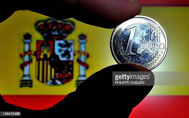 A picture taken on May 29 2012 shows a coin of euro with a Spanish national flag in the background in Lille northern France Spain's sovereign risk...