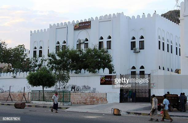 A picture taken on May 3 2016 shows people walking past an Islamic charity council building in the Yemeni port of Mukalla in the Hadramawt province...