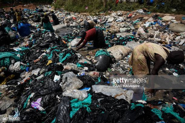 A picture taken on May 30 2018 in Kampala Uganda shows women cleaning plastic bags which are to be sold off to a factory that recycles them into home...