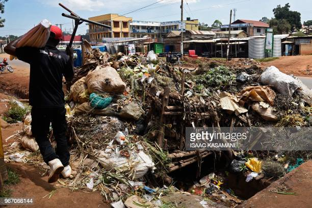 A picture taken on May 30 2018 shows a man walking next to plastic clogged sewage in Kireka On June 5 2018 the United Nations mark the World...