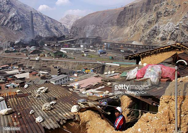 STORY Picture taken on May 31 2007 of a resident of La Oroya peering from the roof of his house above the Doe Run Mining complex in the Andean...
