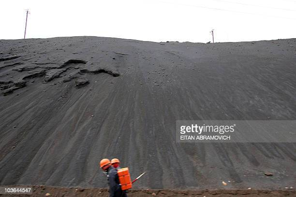 STORY Picture taken on May 31 2007 of two workers of the smelter La Oroya Metal Complex owned by US Doe Run Company next to mount of metal slag in...