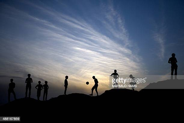 A picture taken on May 4 2014 at sunset shows Palestinian boys playing football in Beit Lahia in the northern Gaza Strip AFP PHOTO /MAHMUD HAMS