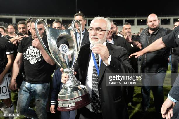 A picture taken on May 6 shows PAOK's GreekRussian president Ivan Savvidis holding the trophy after the cupfinal match between PAOK Thessaloniki and...