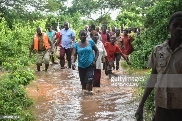 A picture taken on May 7 2018 shows people walking in floodwaters after the Tana River overflowed in Garsen in coastal region of Kenya Flooding...