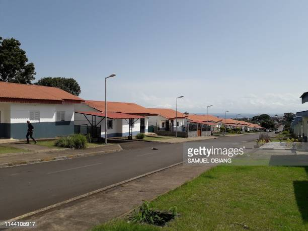 A picture taken on May 8 2019 shows housing estates lined up along a street in the Buena Esperanza neighbourhood of Malabo In a country awash with...