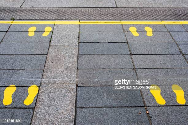 Picture taken on May 8, 2020 shows a tramway dock where yellow footprints had been painted on the ground for people to guard social distancing rules...