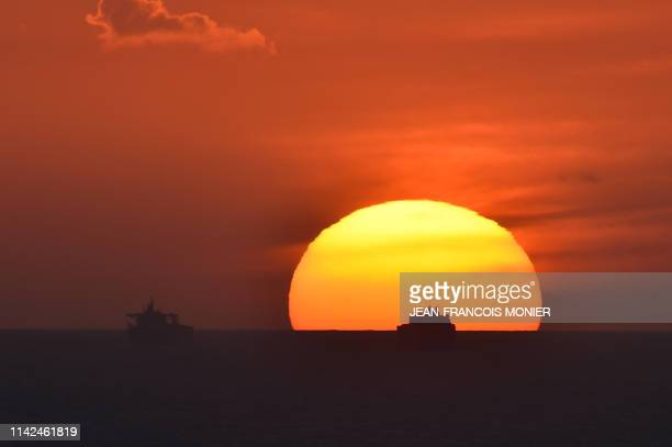TOPSHOT A picture taken on May 9 2019 shows Saudi cargo ship Bahri Yanbu next to British crude oil tanker Nordic Space at sunset waiting to enter the...