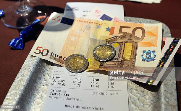 A picture taken on November 10 2012 in a restaurant in Lille shows euro coins and bank notes set up on a bill with the 1960 percent value added tax...