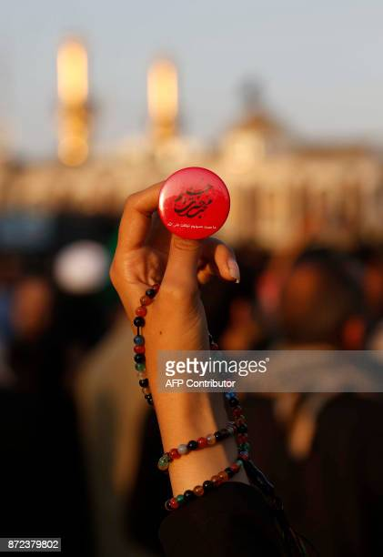 A picture taken on November 10 2017 shows a Shiite pilgrim holding prayer beads and a badge bearing religious text praising the prophet in front of...