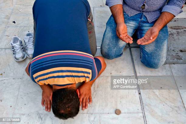 A picture taken on November 10 2017 shows Shiite pilgrims mourning in front of the Immam Hussein shrine in the southern Iraqi city of Karbala during...