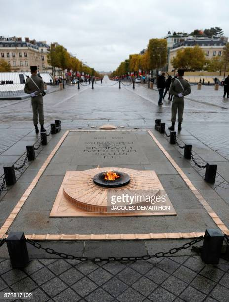 A picture taken on November 11 2017 shows the eternal flame of the Tomb of the Unknown soldier beneath the Arc de Triomphe in Paris during the...