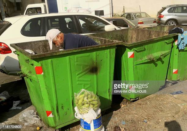 A picture taken on November 11 2019 shows a man searching for food in a garbage container in the northern Lebanese port city of Tripoli Lebanon has...