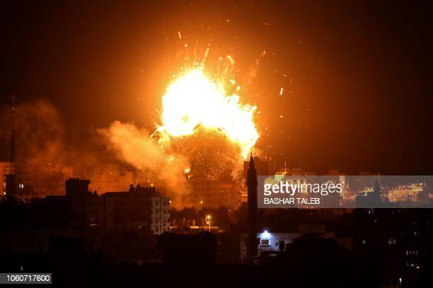 TOPSHOT A picture taken on November 12 2018 shows a ball of fire above the building housing the Hamasrun television station alAqsa TV in Gaza City...
