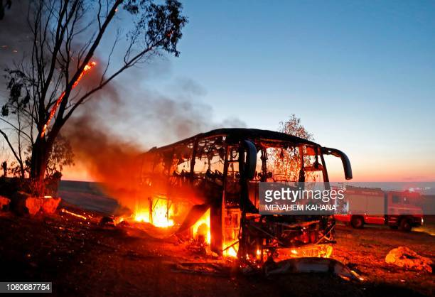 TOPSHOT A picture taken on November 12 2018 shows a bus set ablaze after it was hit by a rocket fired from the Gaza Strip at the IsraelGaza border...