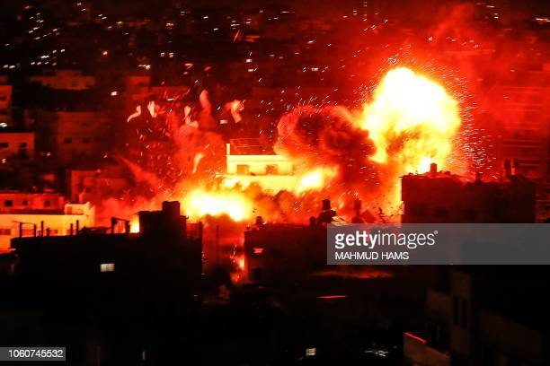 TOPSHOT A picture taken on November 12 shows a ball of fire above the building housing the Hamasrun television station alAqsa TV in the Gaza Strip...