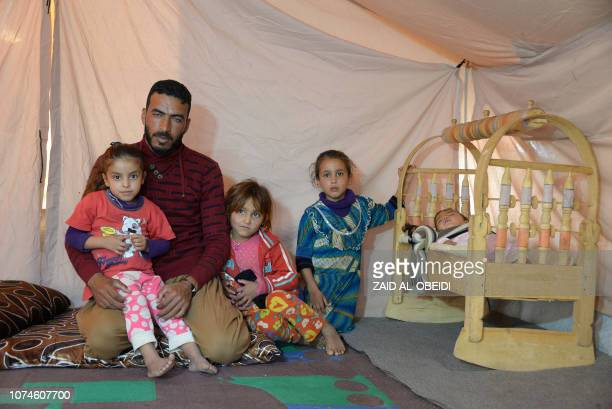 A picture taken on November 12 shows Abdelkhaleq Jouloud sitting with his family in their tent at a camp for displaced people in Hammam alAlil south...
