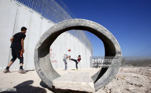 Picture taken on November 12 shows Palestinian children playing football at a make-shift pitch near Israel's controversial separation barrier in the...