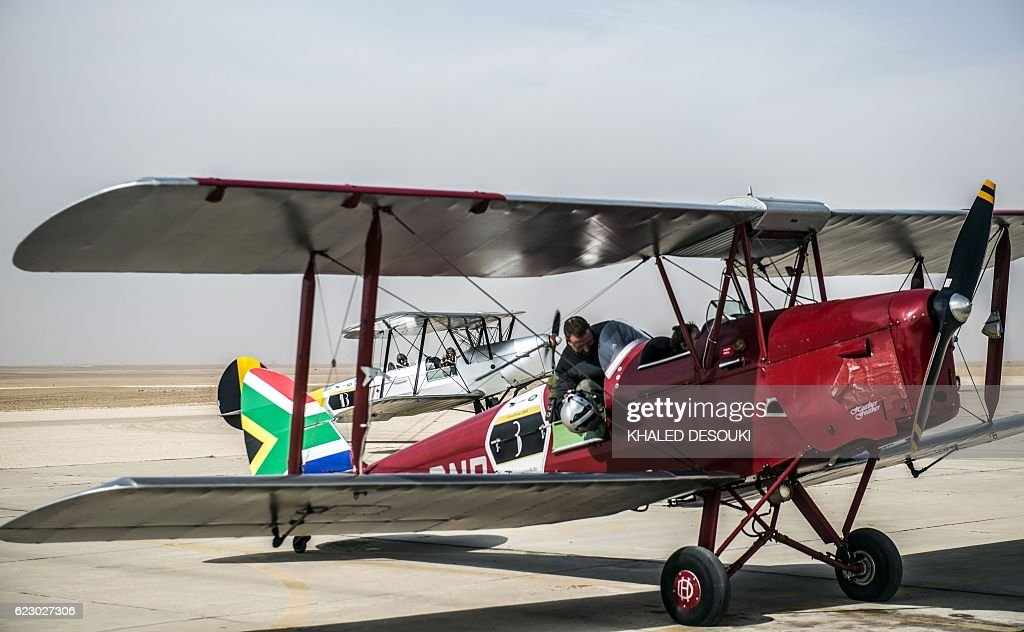 A picture taken on November 13, 2016 shows a pilot sitting in the South Africa team's DH82A Tiger Moth vintage biplane at an airfield in Cairo's 6th of October City, west of the Egyptian capital during the Vintage Air Rally (VAR). A dozen biplanes from the 1920s and 1930s are flying 8,000 miles from Crete to Cape Town in a vintage aviation rally that harks back to the early days of air travel. The pilots will fly along the Nile from Cairo to Khartoum, past the highlands of Ethiopia, down through East Africa past Mount Kilimanjaro, over Victoria Falls, and will end in South Africa. It is the first aviation rally to be granted permission to land at Egypt's Giza pyramids in 50 years, and will put on Sudan's first air show. / AFP / KHALED