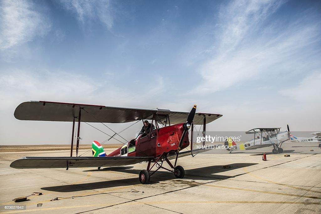 A picture taken on November 13, 2016 shows the DH82A Tiger Moth biplane of the South African team and the Stampe OO-GWB of the Belgium team that are participating in the Vintage Air Rally (VAR) at an airfield in Cairo's 6th of October City, west of the Egyptian capital. A dozen biplanes from the 1920s and 1930s are flying 8,000 miles from Crete to Cape Town in a vintage aviation rally that harks back to the early days of air travel. The pilots will fly along the Nile from Cairo to Khartoum, past the highlands of Ethiopia, down through East Africa past Mount Kilimanjaro, over Victoria Falls, and will end in South Africa. It is the first aviation rally to be granted permission to land at Egypt's Giza pyramids in 50 years, and will put on Sudan's first air show. / AFP / KHALED