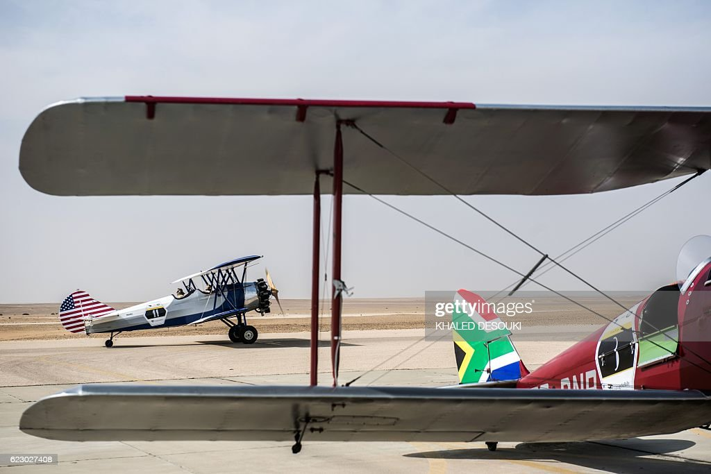 A picture taken on November 13, 2016 shows the Travel Air 4000 vintage biplane of the US team parked on the runway behind the South African DH82A Tiger Moth at an airfield in Cairo's 6th of October City, west of the Egyptian capital, during the Vintage Air Rally (VAR). A dozen biplanes from the 1920s and 1930s are flying 8,000 miles from Crete to Cape Town in a vintage aviation rally that harks back to the early days of air travel. The pilots will fly along the Nile from Cairo to Khartoum, past the highlands of Ethiopia, down through East Africa past Mount Kilimanjaro, over Victoria Falls, and will end in South Africa. It is the first aviation rally to be granted permission to land at Egypt's Giza pyramids in 50 years, and will put on Sudan's first air show. / AFP / KHALED