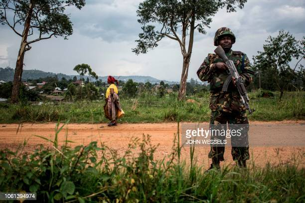 Picture taken on November 13 shows a woman walking by as a Tanzanian soldier from the United Nations Organization Stabilization Mission in the...