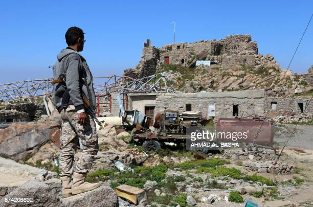 TOPSHOT A picture taken on November 14 2017 shows an armed Yemeni man looking at a communications tower that was destroyed in Saudiled air strikes on...