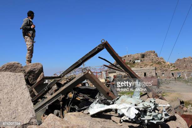 Picture taken on November 14, 2017 shows an armed Yemeni man looking at a communications tower that was destroyed in Saudi-led air strikes on the...